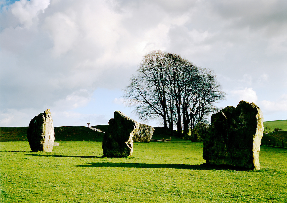 People on encircling earthwork beyond 3 of the standing stones of huge prehistoric stone circle of Avebury, Wiltshire, England.