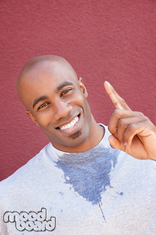 Portrait of a young man with finger pointing upwards over colored background
