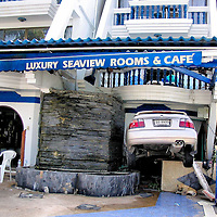 Dog Below Car Wedged in Hotel After Tsunami on Patong Beach in Phuket, Thailand <br />