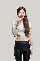 Portrait of beautiful young woman holding ice cream bar over eye against gray background