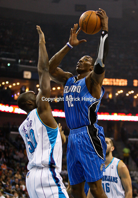 Feb 26, 2010; New Orleans, LA, USA; Orlando Magic center Dwight Howard (12) shoots over New Orleans Hornets center Emeka Okafor (50) during the first quarter at the New Orleans Arena. Mandatory Credit: Derick E. Hingle-US PRESSWIRE
