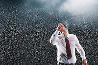 Businessman running hands through wet hair standing in the Rain