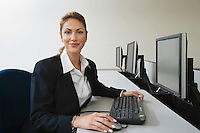 Woman sitting at row of computers, portrait