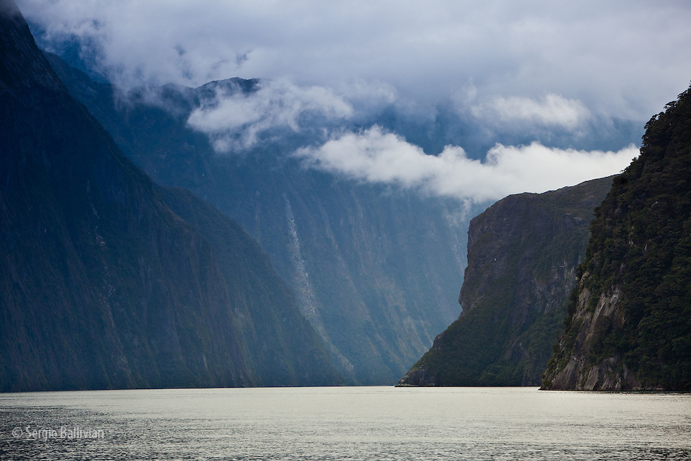 Clouds part below the steep massive cliffs in Milford Sound as the regular rain pattern brings daily rain in New Zealand's South Island.  Cruise ships bring tourists to experience the raw natural beauty of Fiordland National Park in the wet temperate rainforest of southwest New Zealand.