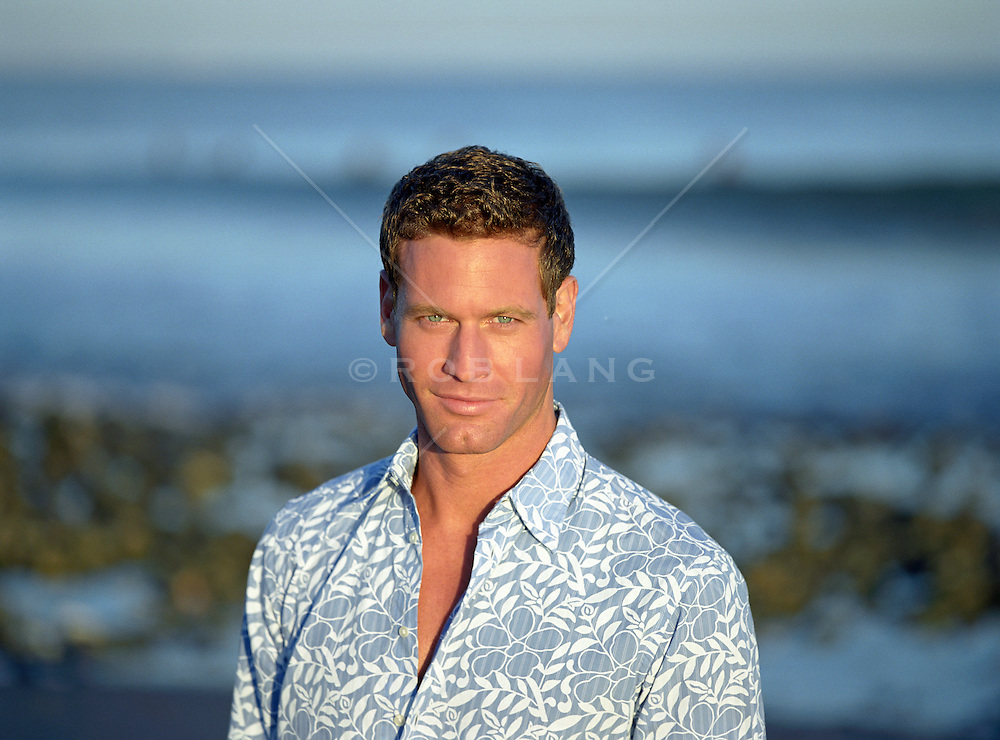 good looking man on the beach at sunset