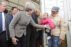 © Licensed to London News Pictures. 13/05/2017. Lisburn, UK. British prime minister THERESA MAY talks to a mother and her young daughter during a visit to Balmoral Show at Balmoral Park in Lisburn, Northern Ireland,  while campaigning ahead of a general election which takes place on June 8, 2017.  Photo credit: Kalista McErlane/LNP