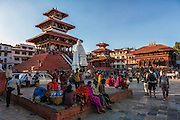 People sit and relax while tourists wander around Kathmandu's Durbar Square.