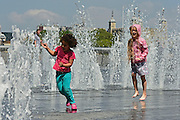 © Licensed to London News Pictures. 31/05/2013. London, UK Children play in the fountains with the Tower of London in the background. Children and office workers enjoy the hot weather near to City Hall and Tower Bridge in London today May 31st 2013. Photo credit : Stephen Simpson/LNP
