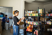 Volunteer Kalisha Webster, 22, of Newark sorts canned goods at the Milpitas Food Pantry in Milpitas, California, on November 25, 2014. (Stan Olszewski/SOSKIphoto)