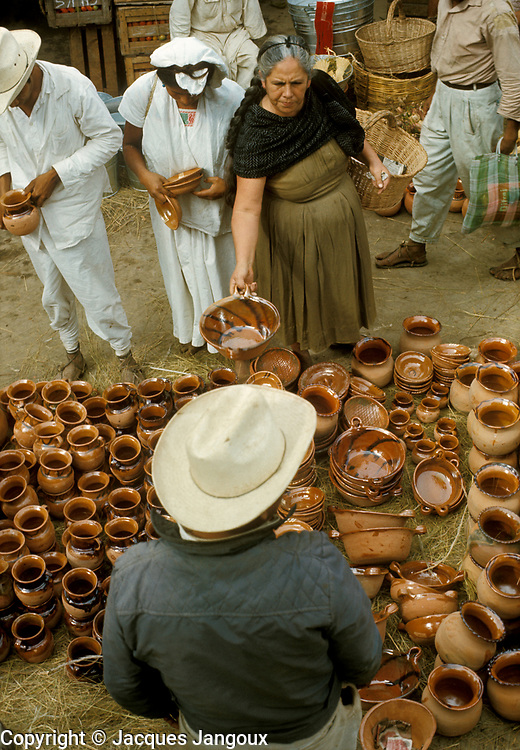 Mexico, Puebla State: Selling clay pots at Sunday market in small town: Cuetzalan.