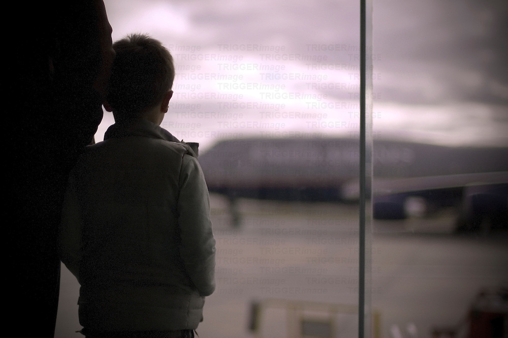 A young boy watching a jumbo jet