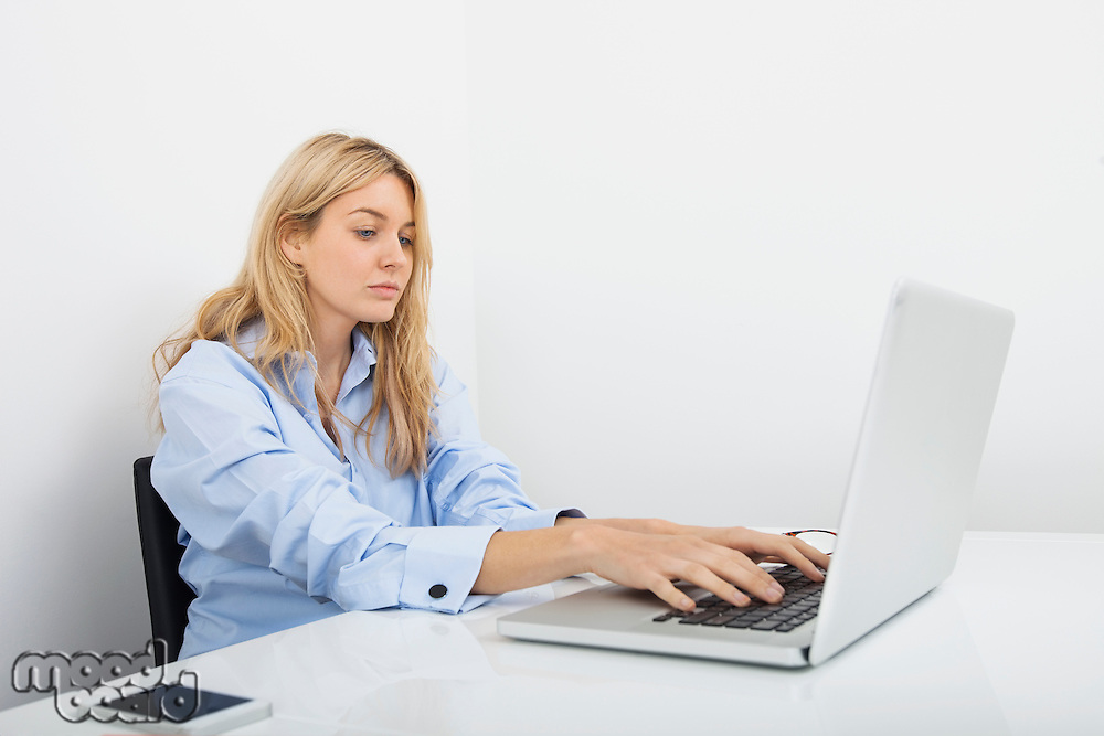 Beautiful young businesswoman using laptop at desk in office
