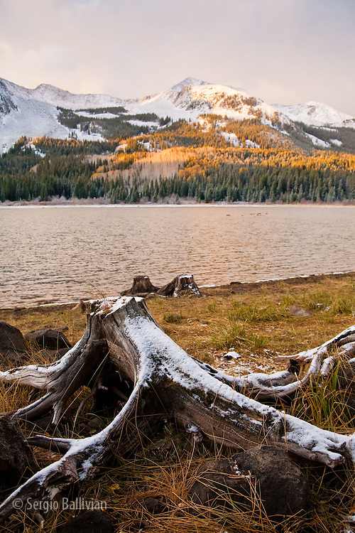 Early morning light scatters across snow-covered peaks above Lost Lake in the Raggeds Wilderness in Colorado.  Autumn in the mountains of Colorado bring a swath of colors and light snow before deep winter snows.