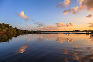 A kayaker paddles at sunset across the tranquil surface of Hidden Lake near the western shore of Biscayne Bay in Miami, Florida.<br />