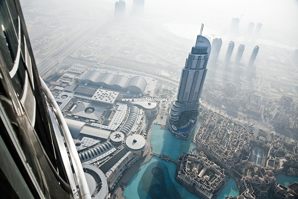 View from the observation deck of Burj Khalifa in Dubai. The Address Downtown Dubai hotel is the main building, with The Dubai Mall, Souk Al Bahar and Dubai Fountain also visible.