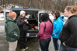 Rachel Wheat, a graduate student at the University of California Santa Cruz, talks to Haines School students about the bird bands she is attaching to the bald eagles in her research study. Since 2009, Haines School students have been conducting a weekly count of bald eagles during the fall semester for the citizen science class at the Haines School in Haines, Alaska. Wheat is conducting a bald eagle migration study of eagles that visit the Chilkat River for her doctoral dissertation. She hopes to learn how closely eagles track salmon availability across time and space. The bald eagles are being tracked using solar-powered GPS satellite transmitters (also known as a PTT - platform transmitter terminal) that attach to the backs of the eagles using a lightweight harness. Along with the bright green leg bands, each of the research bald eagles will receive a silver aluminum U.S. Geologic Survey (USGS) leg band. The bright green leg bands have larger identification information than the USGS bands making it easier to read using binoculars or a spotting scope. Pictured left to right are Pam Randles, Takshanuk Watershed Council Education Director, Wheat, Heidi Kattenhorn, Allison Stuart, and Maggie Martin. During late fall, bald eagles congregate along the Chilkat River to feed on salmon. This gathering of bald eagles in the Alaska Chilkat Bald Eagle Preserve is believed to be one of the largest gatherings of bald eagles in the world.