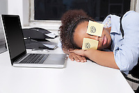 Businesswoman sleeping with sticky notes on eyes at desk in office
