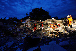 Swiss disaster team search for survivors in the rubble of a collapsed school in Padang, West Sumatra, Indonesia after a powerful earthquake rocked western Indonesia 03 October 2009. The West Sumatra disaster management coordination unit put the death toll from Wednesday's earthquake in Padang and its neighboring town Pariaman at 448, with over 2,000 others injured. Most of the fatalities were found to be in Padang with 197, and Pariaman with 184. Head of the unit Ade Edward added that the quake had severely damaged nearly 12,000 houses, 55 office buildings and 52 places of worship.
