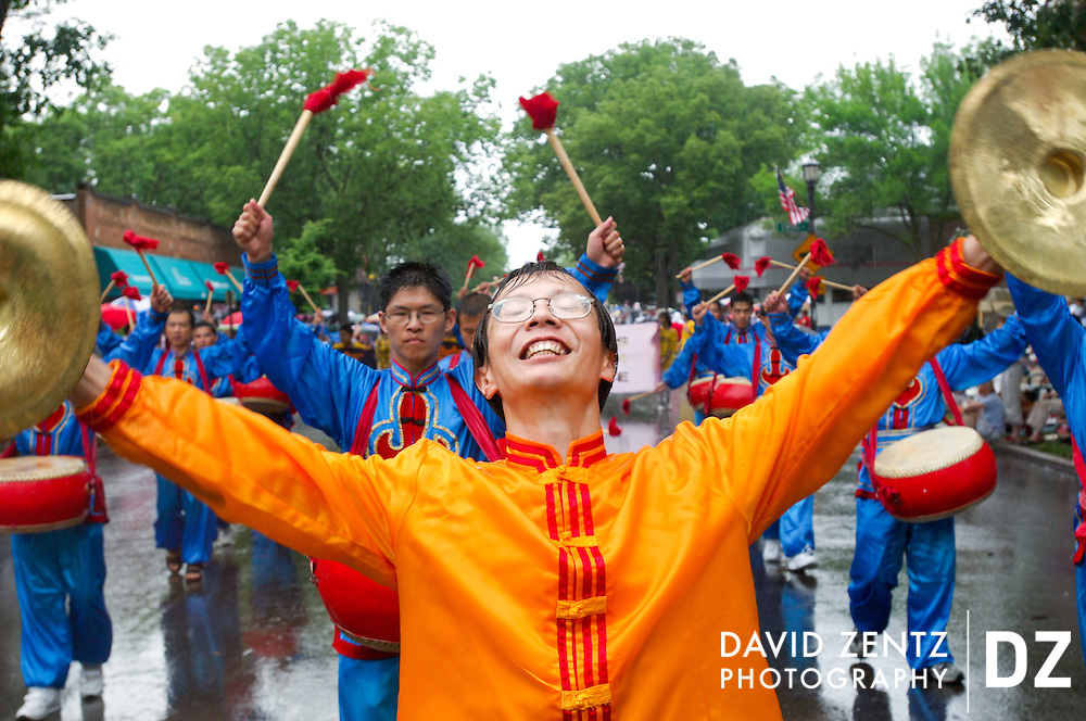 Tony Liu leads Falun Gong drummers as pouring rain falls on the Evanston Fourth of July parade on Central Avenue in Evanston.