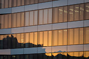 Warm evening sunlight reflected in the windows of generic corporate offices overlooking the river Thames in the heart of the Square Mile, the capital's historical and financial centre, on 1st November 2017, in the City of London, England.