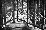 Filtered sunlight strikes scrolled ironwork of a wall in Croissy-sur-Seine, France.  Aspect Ratio 1w x 0.667h.
