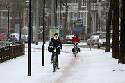 Fietsers rijden op de Zijpendaalseweg in Arnhem door de sneeuw.<br /> <br /> Cyclists at the Zijpendaalseweg in Arnhem in the snow.