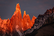 """Sunrise illuminates Cerro Torre (3128 m meters or 10,262 feet elevation), seen from Mirador Condores near Los Glaciares National Park Visitor Center, in El Chalten in Santa Cruz Province, Argentina, Patagonia, South America. Cerro is a Spanish word meaning hill, while Chaltén comes from a Tehuelche word meaning """"smoking mountain"""", due to clouds that usually form around the peaks."""