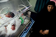 A newborn suffering from a birth defect is lying inside an incubator in the children's ward of Fallujah General Hospital, Iraq, while the grandmother is sitting nearby. (right) Around 15 per cent of children at the hospital are now being born with some sort of congenital defect. The average elsewhere in the world is believed to be between 2 and 4 per cent.