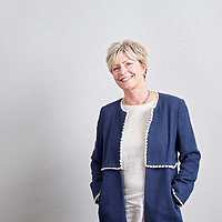 A photograph of a legal recruitment company employee posing for a relaxed portrait in front of a neutral background