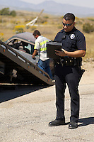 Police officer writing notes, tow truck driver lifting crashed car in background