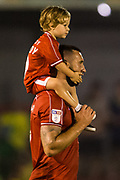 Ollie Palmer (Crawley Town) with a child with 'Daddy' written on the back of their no9 shirt during the EFL Cup match between Crawley Town and Norwich City at The People's Pension Stadium, Crawley, England on 27 August 2019.