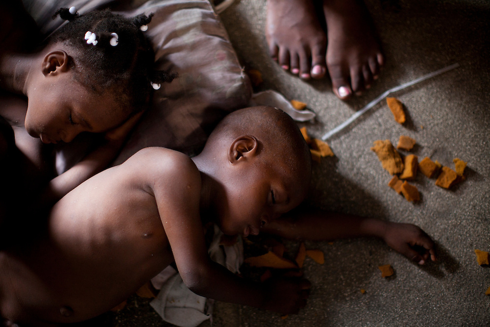 Children sleep on the ground inside a tent in a camp for people displaced by the earthquake on Champs de Mars on July 14, 2010 in Port-au-Prince, Haiti.