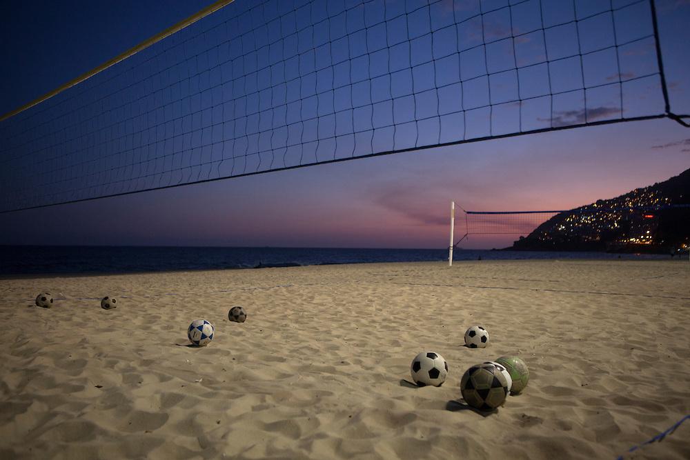 RIO DE JANEIRO, BRAZIL: Voleyballs on the sand at sunset in Ipanema beach.