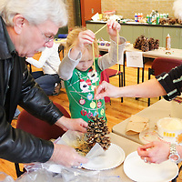 Pete Gaydesh, left, helps his granddaughter Maxton Prigen, 5, make a pine cone bird feeder as Theresa Celia helps Saturday December 20, 2014 during Nature Holiday Creations at Halyburton Park in Wilmington, N.C. (Jason A. Frizzelle)