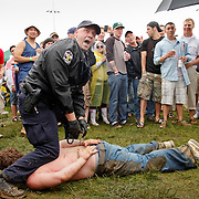 A Louisville Metro police officer arrests an infield partier after he had run across a line of portable restrooms and a gauntlet of beer cans and other projectiles during the 136th running of the Kentucky Derby at Churchill Downs Saturday May 1, 2010. Photo by David Stephenson