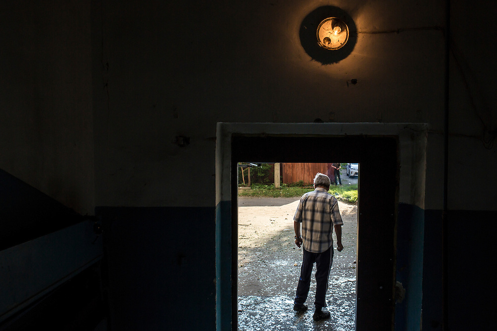 A man walks over broken glass after an apartment building was hit by a suspected grad rocket strike on Tuesday, July 29, 2014 in Donetsk, Ukraine.