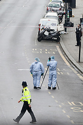 © Licensed to London News Pictures. 24/04/2019. London, UK. A forensic officers at the crime scene on Harlesden High Street, Brent in West London where a 21 year old man was stabbed on Tuesday 23 April 2019 at 9.07pm. According to the Met Police, the suspects arrived in two cars before blocking traffic in order to carry out the attack. The victim fled into a bookmakers (Paddy Power) to seek help before the arrival of emergency services. The victim was pronounced dead at a hospital at 2.47am on Wednesday 24 April 2019. Photo credit: Dinendra Haria/LNP