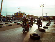 A crowd of people watching motorbike racing.
