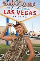Mid-adult woman wearing cowboy hat in front of Welcome to Las Vegas sign, portrait