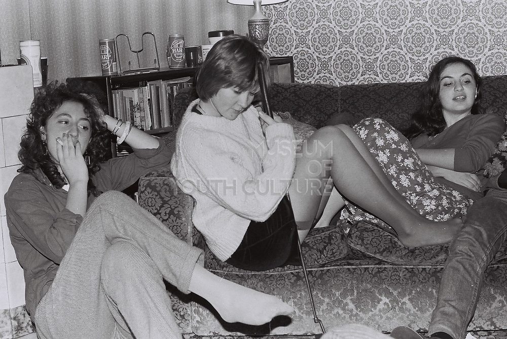Three teenage girls on sofa after a house party, London, UK, 1983