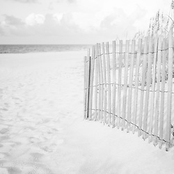 Black and white photo of a beach fence on Casino Beach in Pensacola Beach Florida. Pensacola Beach is a coastal city in the Emerald Coast area of the Southeastern United States. Copyright ⓒ 2018 Paul Velgos with All Rights Reserved.