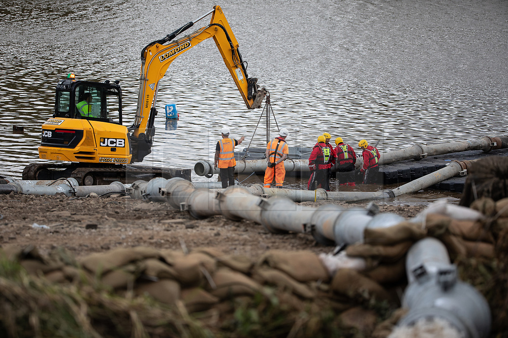 © Licensed to London News Pictures. 05/08/2019. Whaley Bridge, UK. Engineers working on a floating platform in the reservoir connect additional , high-capacity pumping pipes . The town of Whaley Bridge in Derbyshire remains evacuated after heavy rain caused damage to the Toddbrook Reservoir , threatening homes and businesses with flooding . Photo credit: Joel Goodman/LNP