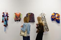 "© Licensed to London News Pictures. 11/05/2017. London, UK. Visitors view colourful garments on display at an exhibition called ""Up and Coming"", in Granary Square King's Cross, featuring works by Central Saint Martins foundation students.   Photo credit : Stephen Chung/LNP"