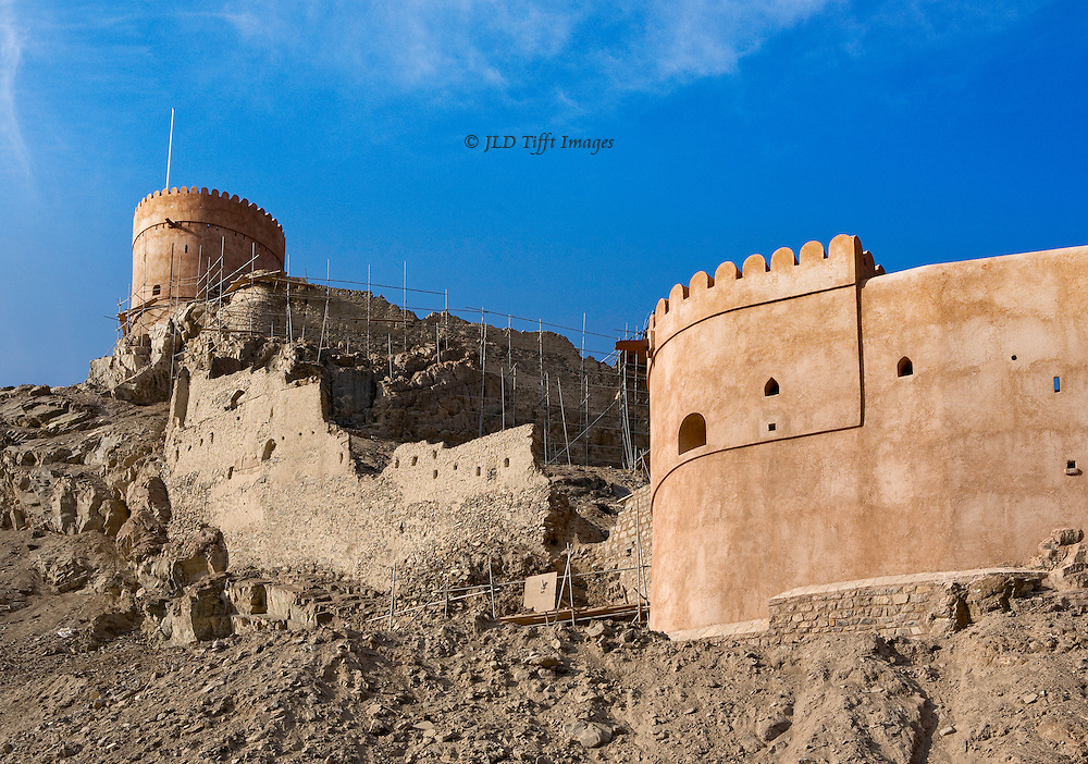 Oman, Samail Fort, partly restored, with its central section still crumbling although a network of fragile bamboo scaffolding suggests that restoration there is being studied or considered.