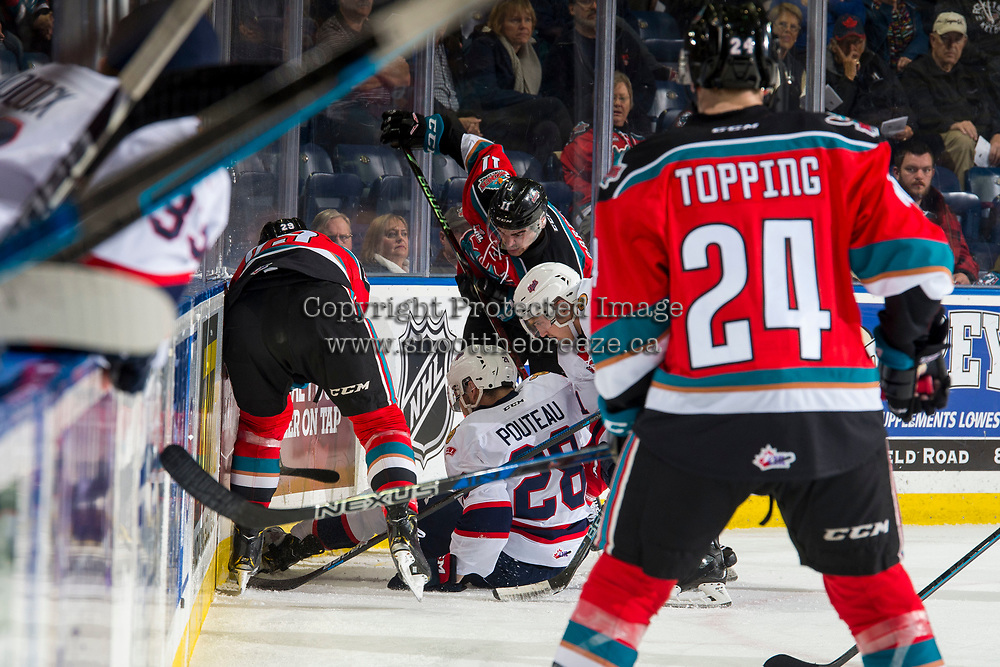 KELOWNA, CANADA - NOVEMBER 21:  Brady Pouteau #28 of the Regina Pats is checked in the corner by Erik Gardiner #11 of the Kelowna Rockets during first period on November 21, 2018 at Prospera Place in Kelowna, British Columbia, Canada.  (Photo by Marissa Baecker/Shoot the Breeze)