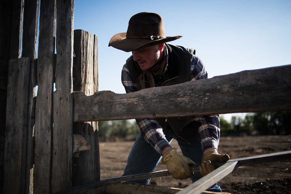 Riley Cihak removes an old water tank from a feed lot on the ranch he works on as a hand in the old abandoned town of in Chance, SD on October 5, 2017. Without a ranch in the family or the sizable savings required to buy a ranch, many locals with the skills to work with cattle work on a freelance basis for ranch owners, though some like Cihak have earned their way to permanent jobs for other ranchers.
