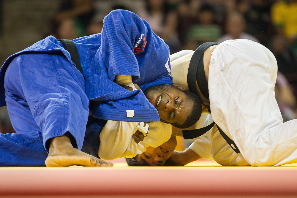 Carlos Tondique (L) of Cuba grapples with Jesus Gavidia of Peru during their 1/8 final contest in the 66kg class at the 2015 Pan American Games in Toronto, Canada, July 12,  2015.  AFP PHOTO/GEOFF ROBINS
