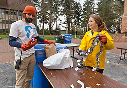 Nick Lorax and Savannah Phalan 15, compare their finds while working on a table of trash during Garbology on Red Square, where grash from different locations is sorted to determine how much is recycleable or compostable at PLU on Tuesday, March 17, 2015. (Photo: John Froschauer/PLU)