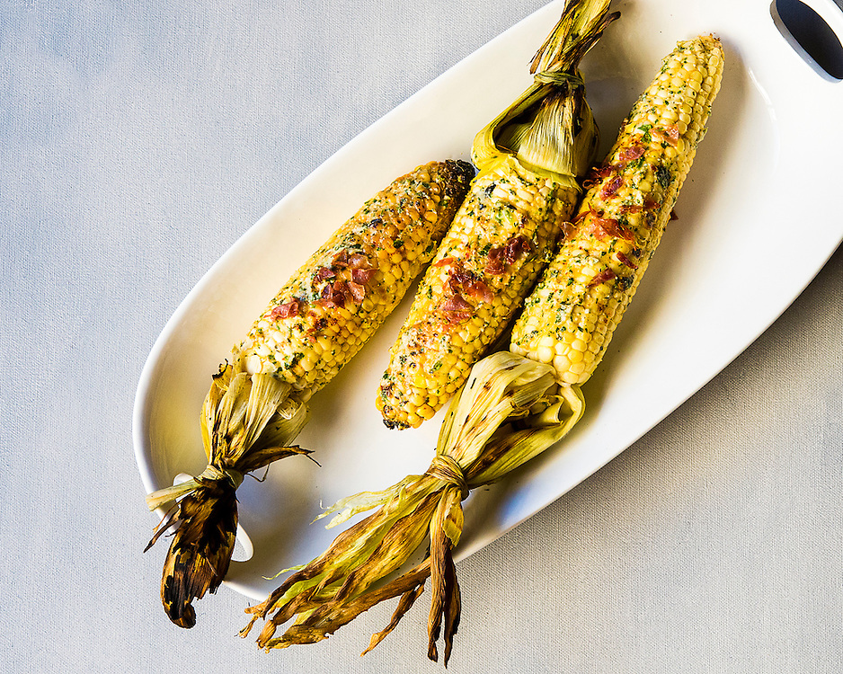 Grilled corn cobs dressed with cheese and herbs spread and proscuitto crumbles