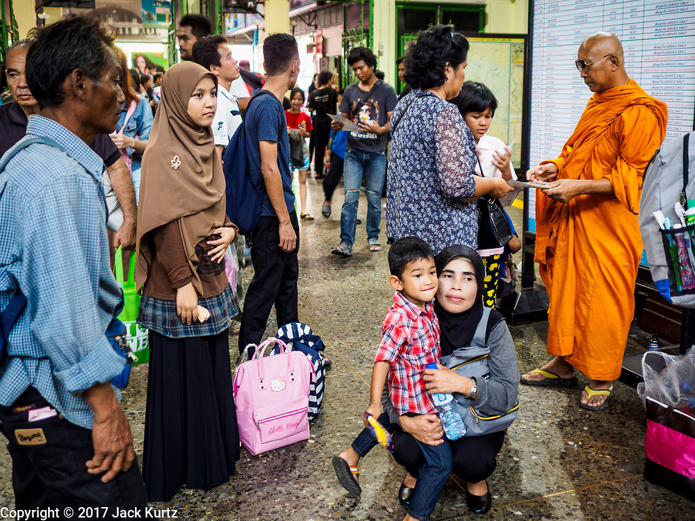 "11 APRIL 2017 - BANGKOK, THAILAND:  Travelers wait in the main waiting room in Hua Lamphong train station during the Songkran travel period at Hua Lamphong train station in Bangkok. Songkran is the traditional Thai Lunar New Year. It is celebrated, under different names, in Thailand, Myanmar, Laos, Cambodia and some parts of Vietnam and China. In most places the holiday is marked by water throwing and water fights and it is sometimes called the ""water festival."" This year's Songkran celebration in Thailand will be more subdued than usual because Thais are still mourning the October 2016 death of their revered Late King, Bhumibol Adulyadej. Songkran is officially a three day holiday, April 13-15, but is frequently celebrated for a full week. Thais start traveling back to their home provinces over the weekend; busses and trains going out of town have been packed.    PHOTO BY JACK KURTZ"